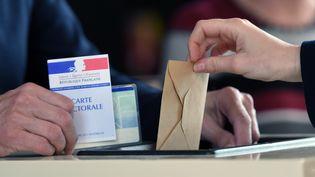 Une électeur français glisse son bulletin de vote dans l'urne à Strasbourg (Bas-Rhin), lors du premier tour de la présidentielle, le 23 avril 2017. (FREDERICK FLORIN / AFP)