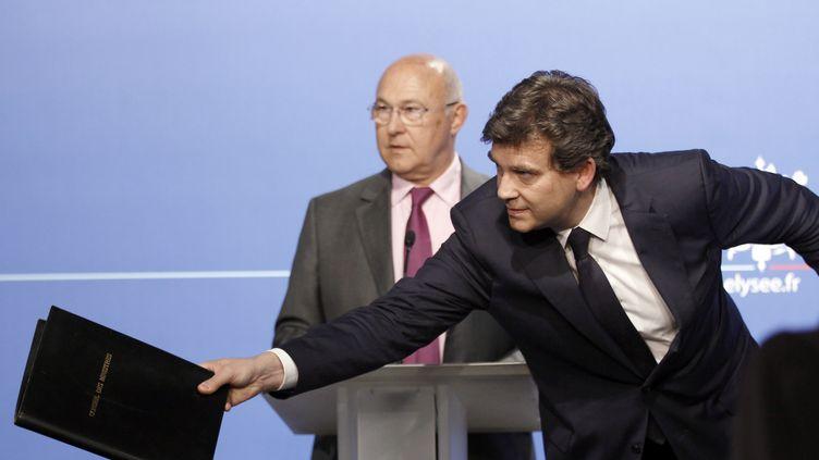 Michel Sapin et Arnaud Montebourg, alors ministres du Travail et du Redressement productif, le 25 juillet 2012 à l'Elysée. (REMY DE LA MAUVINIERE / POOL / AFP)