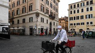 Un cuisinier italien porte un masque pour faire des courses, le 10 mars 2020, à Rome (Italie). (ALBERTO PIZZOLI / AFP)