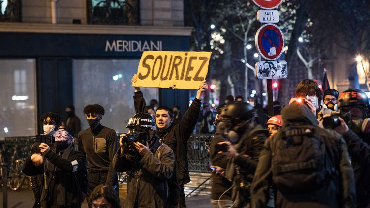 Paris, boulevard Saint-Germain, 17 novembre 2020. Un manifestant et sa pancarte derrière les photographes et journalistes qui protestent contre la proposition de loi relative à la sécurité globale dont certains articles visent à renforcer le contrôle des photos et vidéos de policiers sur les réseaux sociaux. (AMAURY CORNU / HANS LUCAS / AFP)