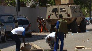 Des agents de sécurité se déplacent à côté d'un véhicule blindé à la suite de multiples attaques à Ouagadougou contre notamment le QG militaire qui ont causé la mort de 8 soldats et beaucoup d'autres blessés le 2 mars 2018. (Ahmed Ouoba/AFP)