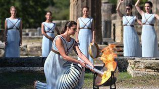 L'actrice grecque Xanthi Georgiou, jouant le rôle de la grande prêtresse, a allumé la torche lors de la cérémonie d'allumage de la flamme des Jeux olympiques d'hiver de Pékin 2022 sur le site archéologique d'Olympie, berceau des Jeux olympiques antiques, le 18 octobre 2021. (ARIS MESSINIS / AFP)