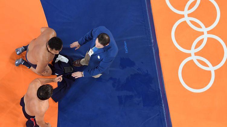 Les deux entraîneurs mongols protestent devant les juges (LAURENT KALFALA / AFP)