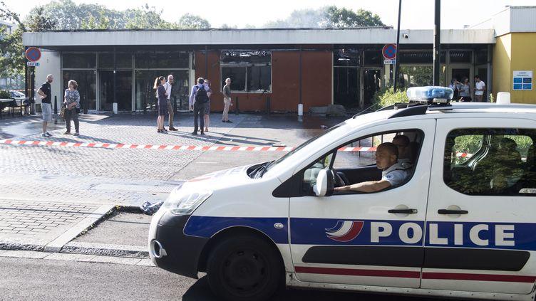 Une voiture de police passe devant un bâtiment incendié, le 4 juillet 2018, dans le quartier de Breil, à Nantes, au lendemain d'une nuit d'émeutes consécutives à la mort d'un jeune conducteur de 22 ans touché par un tir de la police. (SEBASTIEN SALOM GOMIS / AFP)
