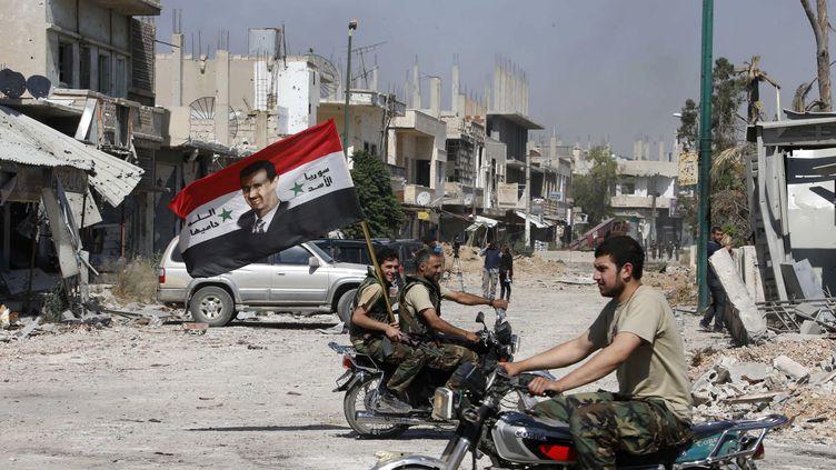 Des soldats de l'armée loyaliste brandissent un drapeau syrien et un portrait de Bachar Al-Assad, à Qousseir,le 5 juin 2013. (MOHAMED AZAKIR / REUTERS)