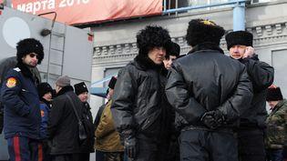 """Des hommes vêtus d'uniformes cosaques postés devant le Centre Sakharov, à Moscou, où était joué une pièce évoquant le procès des Pussy Riaot, """"Les Procès de Moscou"""" du Suisse Milo Rau, le 3 mars 2013  (ADNREY SMIRNOV / AFP)"""