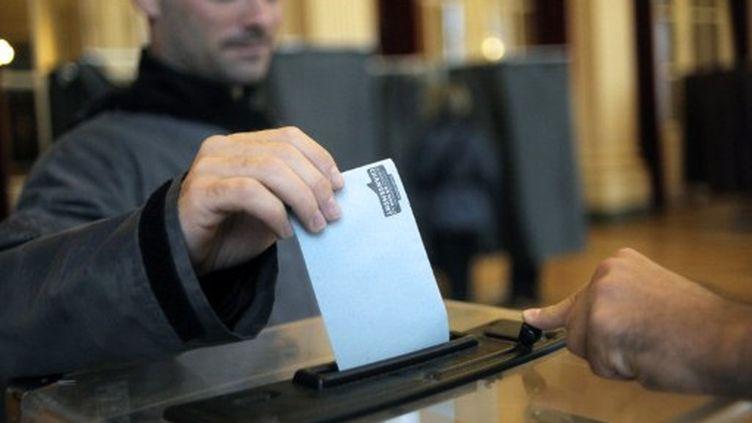 Vote dimanche dans un bureau de vote parisien. (JEFF PACHOUD / AFP)