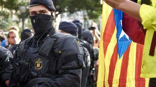 Un manifestant brandit un drapeau catalan sous les yeux d'un policier, le 19 octobre 2019 à Barcelone (Espagne). (IRANZU LARRASOANA ONECA / NURPHOTO / AFP)