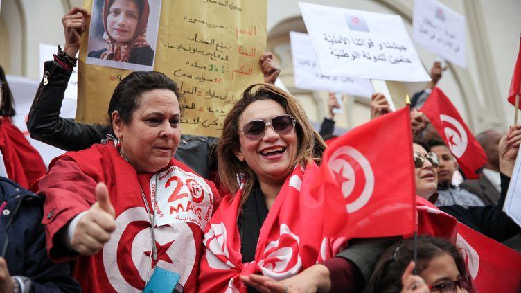 Des Tunisiennes brandissent des drapeaux lors d'une manifestation organisée par des femmes à l'occasion de la fête de l'indépendance à Tunis, le 20 mars 2019. (CHEDLY BEN IBRAHIM / NURPHOTO)