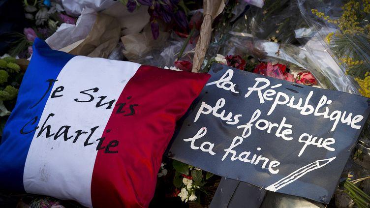 """Dessymboles de soutien déposés devant le siège de """"Charlie Hebdo"""", le 7 février 2015. Un mouvement de solidarité hors du commun avait uni la France aprèsl'attaque contrel'hebdomadaire satirique qui avait marqué le début de la vague d'attentats de janvier. (JOEL SAGET / AFP)"""