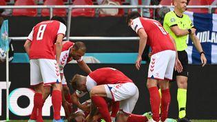 Des joueurs danois aident leur coéquipier Christian Eriksen après qu'il se soit effondré avant l'arrivée des médecins, lors du match del'Euro face à la Finlande au stade Parken à Copenhague, le 12 juin 2021. (JONATHAN NACKSTRAND / AFP)