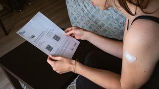Une femme en possession de son certificat de vaccination après avoir reçu une injection de vaccin contre le Covid-19, à Paris, le 21 mai 2021. (LEO PIERRE / HANS LUCAS / AFP)