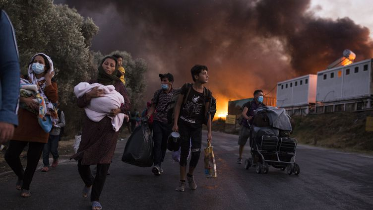 Desmigrants fuient le camp de réfugiés de Moria, ravagé par un gigantesqueaccident, sur l'île de Lesbos, le 9 septembre 2020. (SOCRATES BALTAGIANNIS / DPA / MAXPPP)