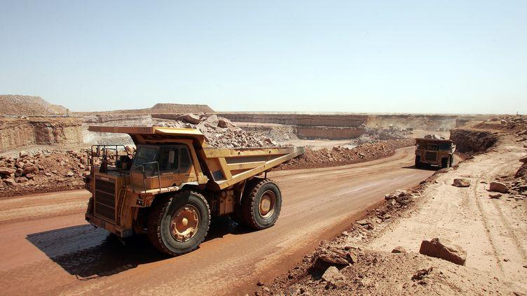 Des camions de la Somaïr (société des mines de l'Aïr) transportent de la roche contenant de l'uranium de la mine à ciel ouvert d'Arlit (Niger), dans le désert de l'Aïr, le 23 février 2005. (PIERRE VERDY / AFP)