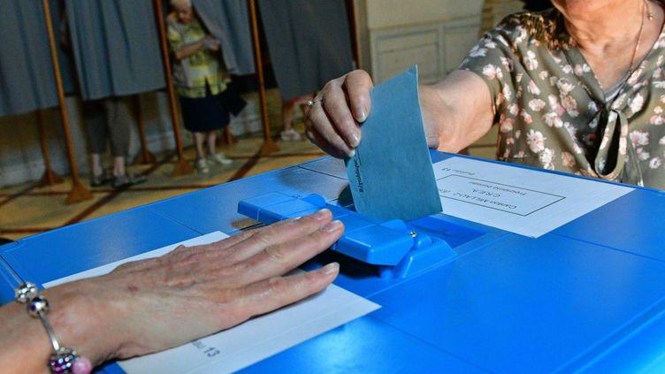 un bulletin de vote s'apprète à être déposé dans une urne pour le vote du premier tour des législatives, à Millau (Aveyron), le 11 juin 2017. (MAXPPP)