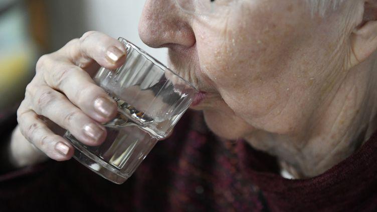 Une personne âgée boit un verre d'ea, le 19 juin 2017 à Quimper. (FRED TANNEAU / AFP)