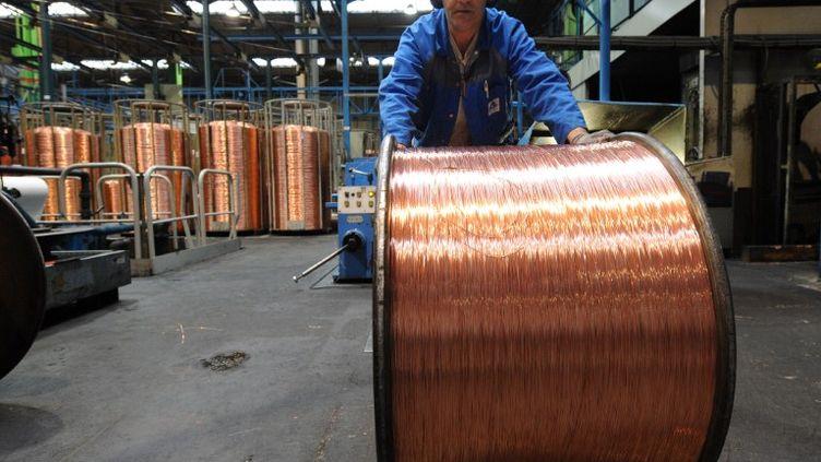 Un des 1000 salariés associés de l'entreprise Acome, spécialisée dans la fabrication de câbles, fait avancer une bobine de fil de cuivre, le 5 janvier 2012 à Romagny (Manche). (JEAN-FRANCOIS MONIER / AFP)