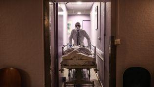 Un employé des pompes funèbres conduit un corps vers un cercueil, le 17 avril 2020, à Lyon. (ANTOINE MERLET / HANS LUCAS / AFP)