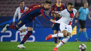 Le défenseur du FC Barcelone,Gerard Pique, face à l'attaquant du PSG,Kylian Mbappé, en huitième de finale aller de la Ligue des champions, le 16 février 2021. (LLUIS GENE / AFP)