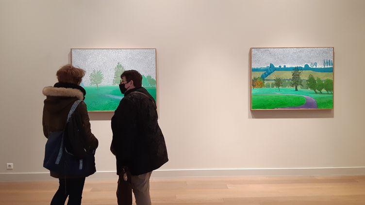 Des visiteurs à la galerie Lelong devant des peintures de David Hockney. (ANNE CHEPEAU / RADIO FRANCE)