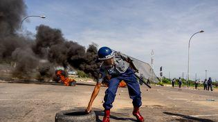 Un policier dégage un pneu de la chaussée, lors d'émeutes à Bulawayo au Zimbabwe, le 14 janvier 2019. (ZINYANGE AUNTONY / AFP)