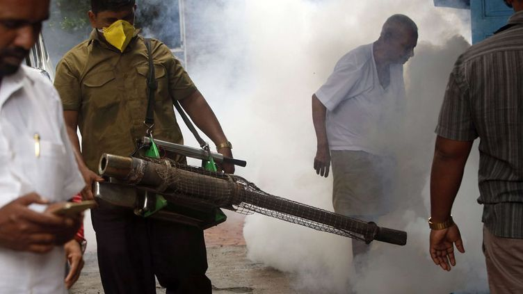 Un agent municipal répand de la fumée près d'une gare de la ville, le 3 septembre 2016. La période est critique alors que plus de 50% des habitants s'entassent dans des bidonvilles. Et que les pluies de mousson s'abattent sur Bombay, provoquant un pic de maladies tropicales. (Rajanish Kakade/AP/SIPA)