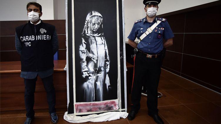 Des policiers italiens à côté de l'œuvre attribuée à Bansky et volée au Bataclan, à L'Aquila, le 11 juin 2020. (FILIPPO MONTEFORTE / AFP)