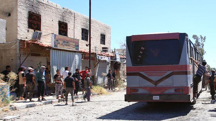 Des rebelles syriens, autour d'un bus à Qadam, un quartier du sud de Damas aux mains des jihadistes, le 21 août 2014. (YOUSSEF KARWASHAN / AFP)