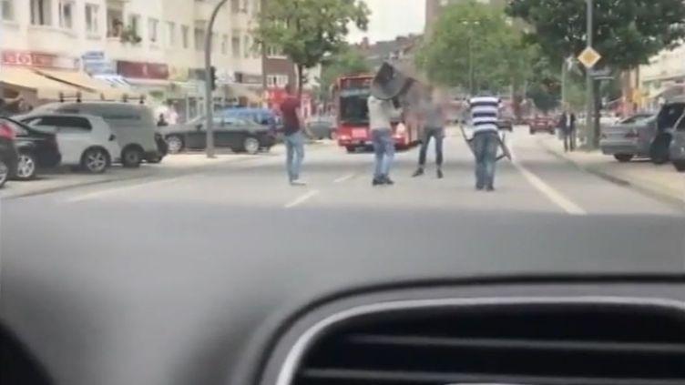 Des personnes, armées de chaises et de fauteuils, tentent d'encercler un homme suspecté d'avoir mené une attaque au couteau qui a fait un mort et six blessés, à Hambourg (Allemagne), le 28 juillet 2017. (FRANCE TELEVISIONS)