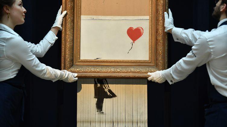 """""""Love Is in the Bin"""", l'œuvre du street-artiste Banksy qui s'est autodétruite, le 12 octobre 2018, à Londres. (BEN STANSALL / AFP)"""