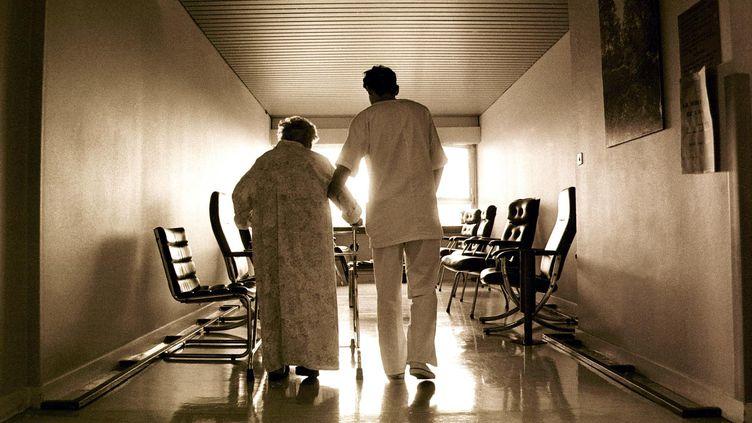 Un infirmier accompagne une personne âgée dans le couloir de l'unité de soins palliatifs de l'hôpital de La Rochelle. (AUGE / SIPA)