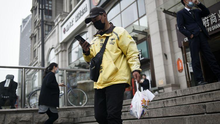 Un livreur portant un masque, à Pékin (Chine), le 15 avril 2020. (WANG ZHAO / AFP)