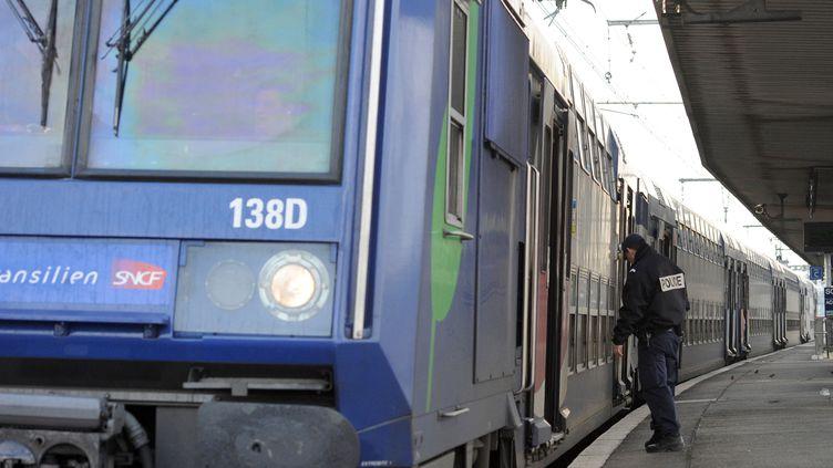 Un policier s'apprête à monter à bord d'un Transilien en région francilienne. (MIGUEL MEDINA / AFP)