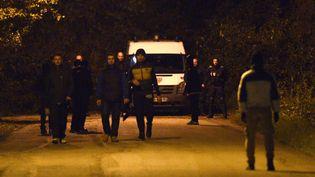 Des migrants près d'un car de CRS à Calais, le 10 novembre 2015. (DENIS CHARLET / AFP)