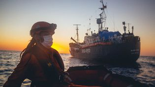 """Une membre de l'ONG allemande Sea-Eye près du navire """"Alan Kurdi"""", le 6 avril 2020 en Méditerranée. (CEDRIC FETTOUCHE / SEA-EYE.ORG / AFP)"""