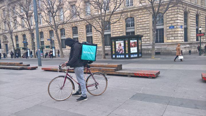 Un livreur (qui n'a pas été interrogé dans le cadre de notre article) attend une commande en consultant son téléphone portable, place de la République, à Paris. (F. MAGNENOU / FRANCEINFO)