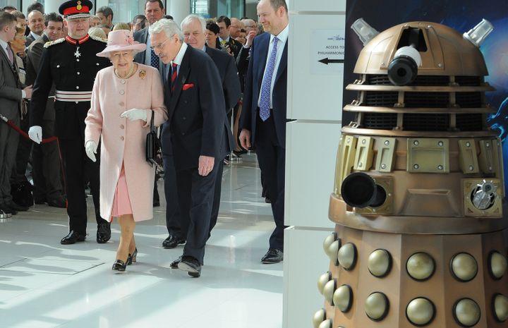 La reine d'Angeleterre Elizabeth II visite MediaCity, à Salford (Royaume-Uni), le 23 mars 2012. A droite, un Dalek guette. (ANDREW YATES / AFP)