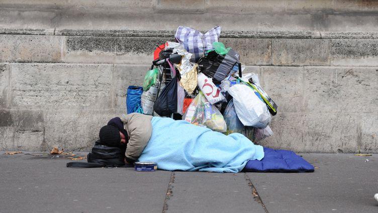 Un mendiant couché dans un sac de couchage dans la rue avec ses affaires à Paris. (NATHANAEL CHARBONNIER / FRANCE-INFO / RADIO FRANCE)