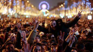 Des fêtards rassemblés sur les Champs-Elysées, à Paris, pour fêter le Nouvel An, le 1er janvier 2017. (GEOFFROY VAN DER HASSELT / ANADOLU AGENCY / AFP)