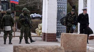 Des militaires ukrainiens (à droite), quittant le quartier général de la marine ukrainienne à Sebastopol (Crimée), passé sous le contrôle de milices pro-russes (à gauche), le 19 mars 2014. (FILIPPO MONTEFORTE / AFP)
