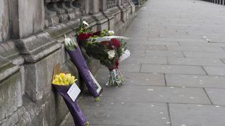 Les fleurs déposées contre le palais de Westminster à Londres le 23 mars 2017. (IK ALDAMA / AFP)