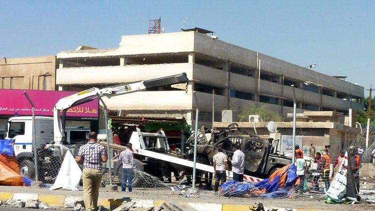 Les débris d'une voiture calcinée après l'attentat deJadida, à Bagdad, le 30 septembre 2013. (SABAH ARAR / AFP)