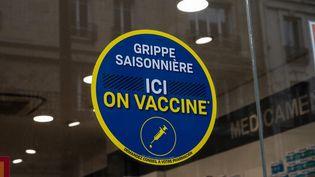 Une affiche pour le vaccin contre la grippe saisonnière sur la vitrine d'une pharmacie, à Paris, le 20 janvier 2021. (RICCARDO MILANI / HANS LUCAS / AFP)
