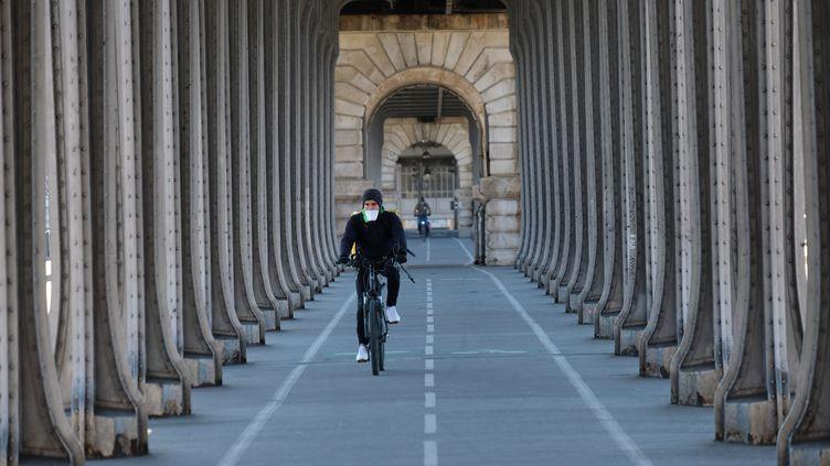 Un cycliste portant un masque FFP2 sur le pont de Bir-Hakeim, 23 mars 2020 à Paris en pleine période de confinement. (NATHANAEL CHARBONNIER / ESP - REDA INTERNATIONALE)