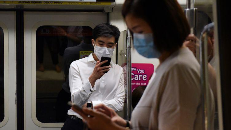 Des passagers du Mass Rapid Transit portent des masques faciaux comme mesure préventive contre le coronavirus Covid-19 à Singapour, le 18 mars 2020. (CATHERINE LAI / AFP)