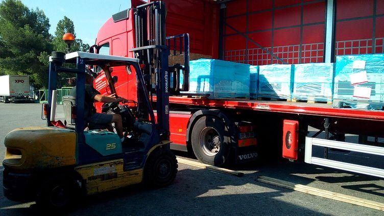 Un transporteur routier charge son camion avant de prendre la route vers l'Italie (Evan Lebastard / RADIO FRANCE)