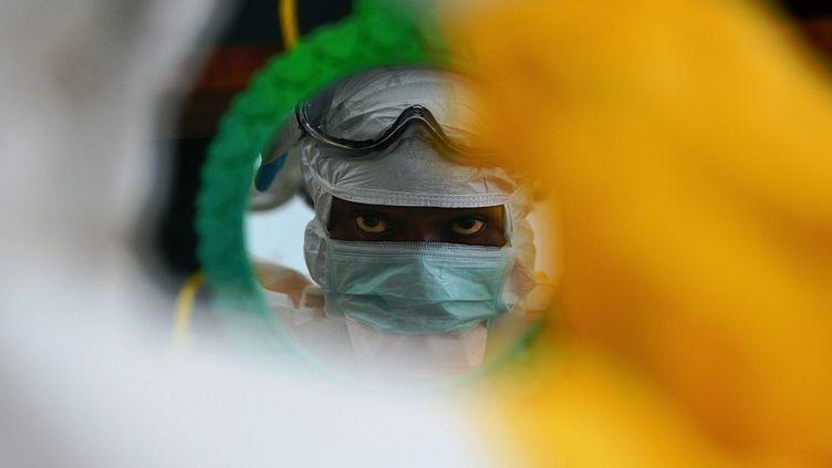 Médecin de MSF vérifiant ses vêtements de protection dans un miroir à Kailahun, épicentre de la pire épidémie d'Ebola au monde, le 15 août 2014au Sierra Leone. (CARL DE SOUZA / AFP)