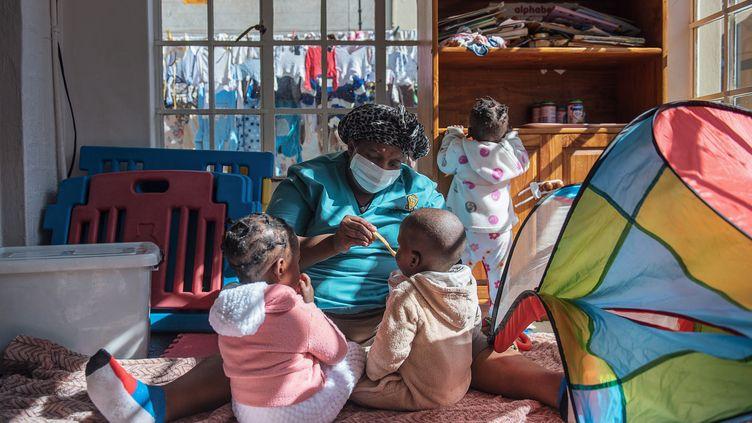 Une infirmière donne à manger à des enfants abandonnés dans un orphelinat de Johannesburg le 27 juin 2019.  (MICHELE SPATARI / AFP)