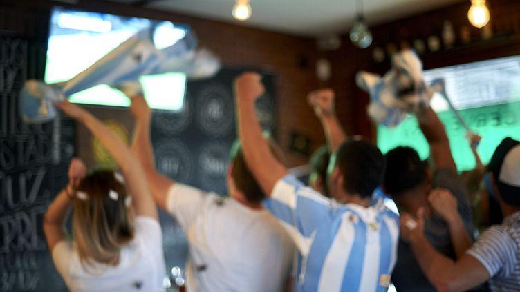 Des supporters regardent un match de football dans un bar (photo d'illustration). (FREDERIC CIROU / ALTOPRESS / AFP)