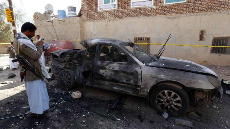 Une voiture carbonisée à l'extérieur d'une mosquée de Sanaa, la capitale yéménite, visée par l'un des trois attentats-suicides survenus le 20 mars 2015. (MOHAMMED HAMOUD / ANADOLU AGENCY / AFP)